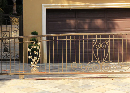 hand made decorative gold tinted sliding gate and hinged pedestrian gate