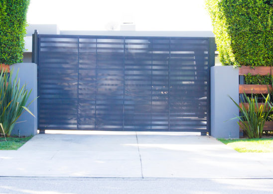 custom black steel single slide gate with laser etched privacy screen