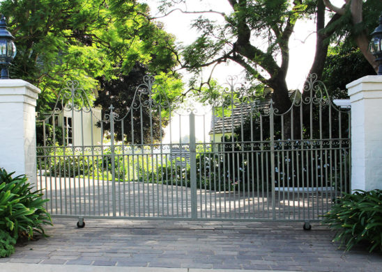 dual sliding gates with hand painted steel and vertical spindels
