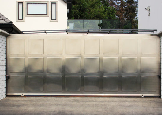 single slide auto gate in contemporary stainless steel with medallions