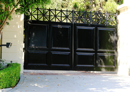 custom built wood paneled bifold auto entry gate