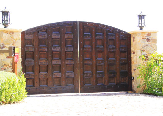 bifold custom wood auto gate with forged iron rivets