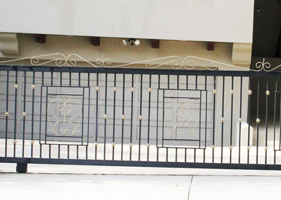 black wrought iron with faux brass accents auto sliding gate