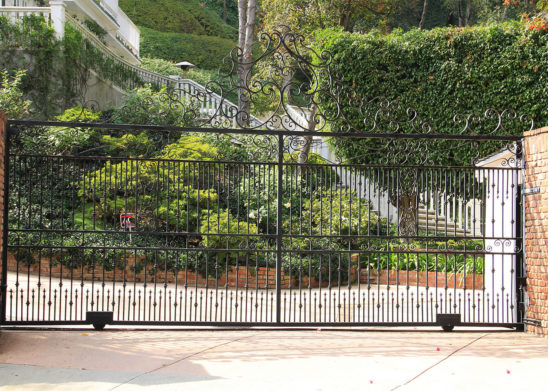 wrought iron sliding auto gate with vertical spindles and scrolled top