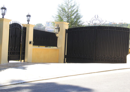 black wrought iron and sheet metal pedestrian and auto gates