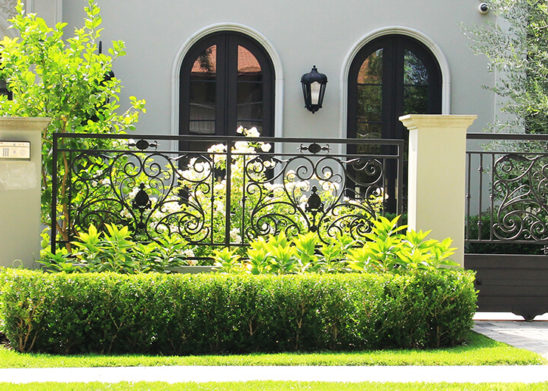 black wrought iron and sheet metal sliding auto  gate and hinged pedestrian gate